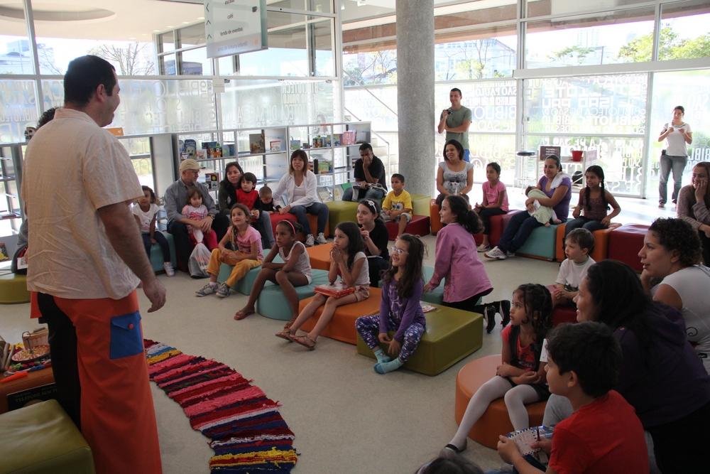 Crianças, sentadas em pufes na biblioteca, prestam atenção à história que está sendo contada por ator.