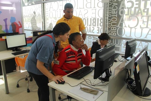 Funcionários da BSP orientam senhora a usar o computador.