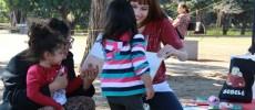 Funcionária da BSP, ajoelhada, segura um livro e o mostra para criança que, em pé e de costas, presta atenção. A cena se passa no Parque da Juventude.