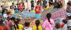 Rosita Flores, da Cia. Duo Encantado, conta histórias para a criançada do Parque da Juventude. Ela está no centro de uma roda, com uma saia enorme, rodada, com muitas fitas. Cada criança está segurando uma fita.