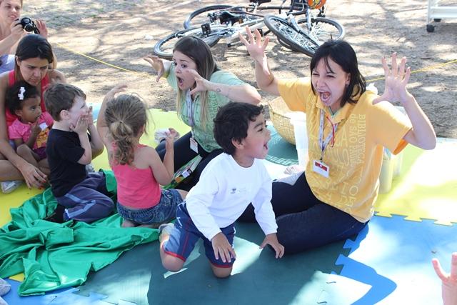 Funcionária da BSP brinca com crianças durante Bebelê, no Parque da Juventude. Ela e um menino parecem imitar um monstro. Estão com os braços para cima e a boca aberta, tipo um urro.