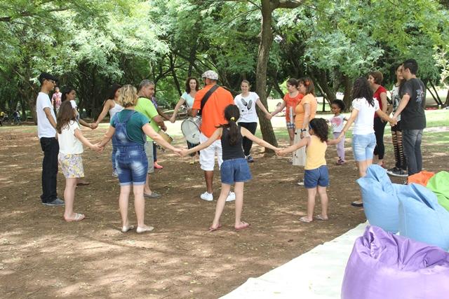 Durante a atividade Domingo no Parque, de contação de histórias e leitura no Parque da Juventude, os participantes cantam e fazem uma roda embaixo das árvores.