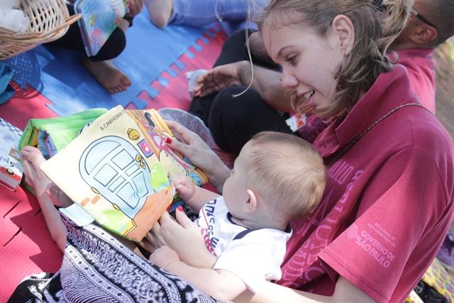 Funcionária da BSP lê livrinho com bebê, que está sentado em seu colo.