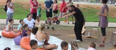 Contação de histórias no Parque da Juventude. Público, sentado e deitado no chão, entre crianças e adultos, prestam atenção à performance de dois atores. Ao fundo, algumas pessoas também conferem a apresentação de pé.