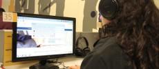 Garota usa novo software instalado nos computadores da BSP. Ela está na BSP, de costas, olhando para a tela do computador, com um fone na cabeça.