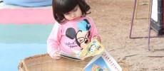 Menina de cerca de 4, 5 anos procura livrinhos em uma cesta de livros, no Parque da Juventude. Ela tem cabelinho curto, escuro, liso, e blusa rosa da Minnie.