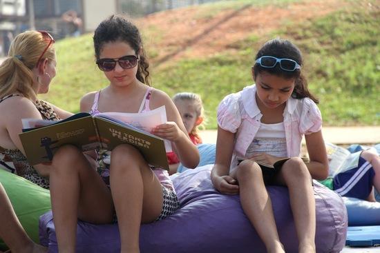 Duas meninas leem no Parque da Juventude durante o Domingo no Parque, programa da Biblioteca de São Paulo que ocorre aos domingos