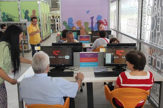 Alunos idosos sentados em frente aos computadores da BSP aprendem a usar a máquina. Em primeiro plano, de costas, um senhor de cabelos brancos e camisa azul e uma senhora com blusa de listras brancas e vermelhas horizontais
